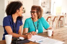 caregiver and elder talking and filling up form