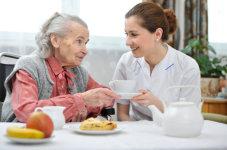 caregiver serving milk to an elder