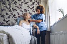 caregiver assisting elder in dressing