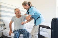 caregiver assisting elder in standing
