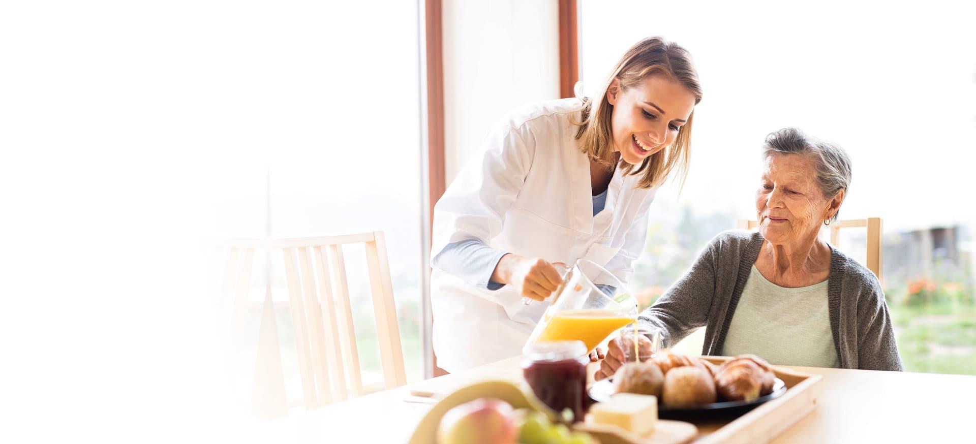 caregiver serving the elder's breakfast