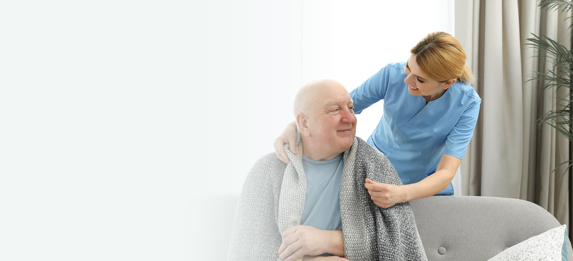 caregiver giving blanket to an elder