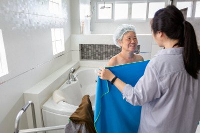 caregiver giving towel to senior woman
