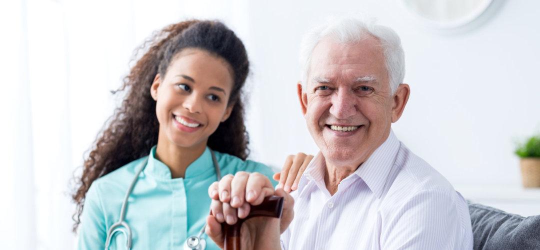 senior man and her caregiver smiling